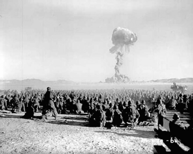 Soldiers watch an atom bomb test.
